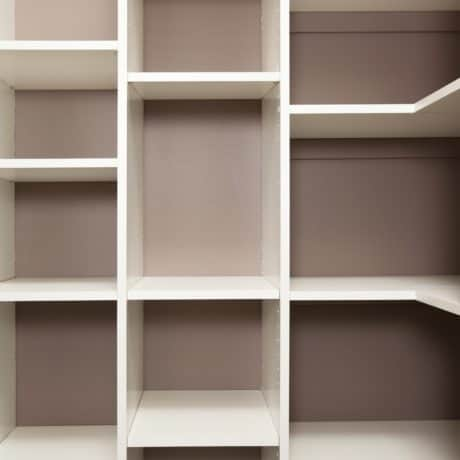 An empty house pantry or closet space efficient wall shelving cubby system.