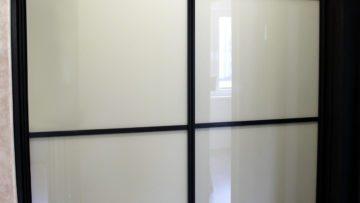 Brown wardrobe with white glass sliding doors
