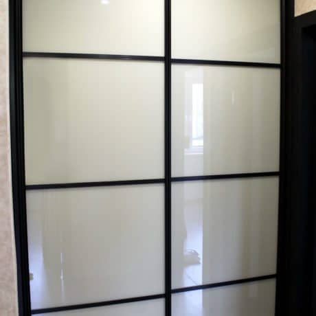Brown wardrobe with white glass sliding doors