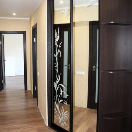 Brown wardrobe with sliding glass doors in the hallway.